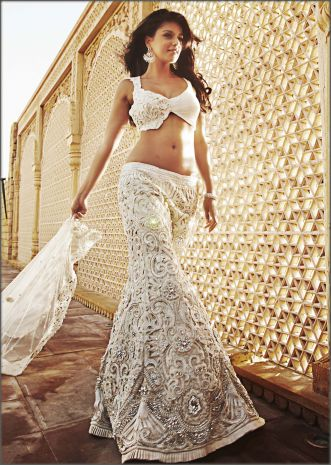 Off white cutwork lehenga by Kalki.The blouse can be customized into a corset also
