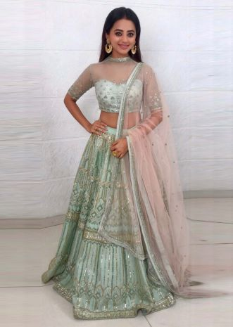 Pistachio green embellished net lehenga paired with a matching net blouse and light cream net dupatta