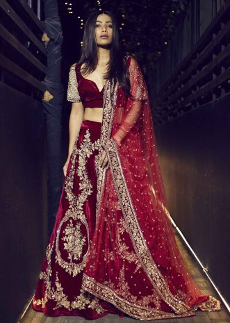 Featuring red velvet lehenga embellished in floral motif embroidery