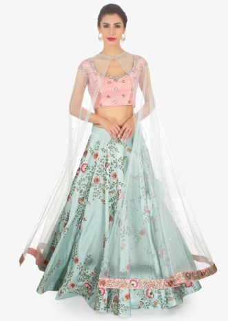 Blue raw silk lehenga paired with peach blouse and a matching net cape