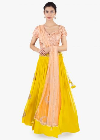 Canary yellow georgette skirt paired with a peach top and peach net dupatta