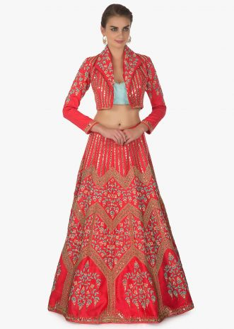 Coral lehenga paired with mint green strapless blouse and coral jacket