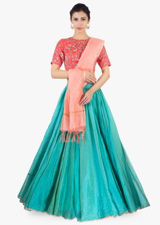 Coral organza blouse paired with  jungle  green shade organza lehenga