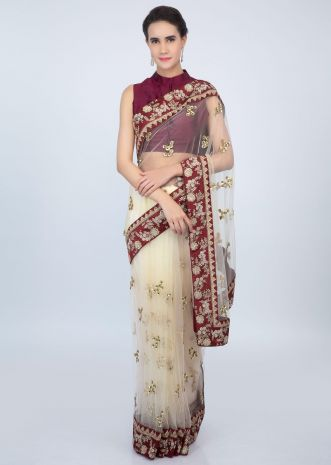 Cream sheer net embroidered saree with contrasting wine raw silk border only on kalki