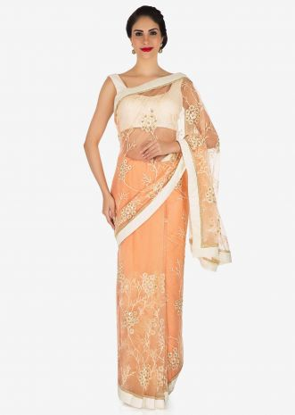 Net saree featuring in peach with white embroidered butti and scalloped border only on Kalki