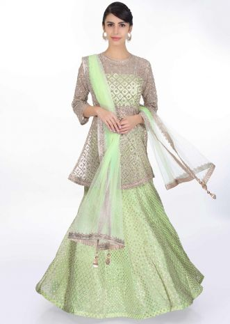 Pista green weaved lehenga paired with a strap crop top along with embroidered net top layer and net dupatta
