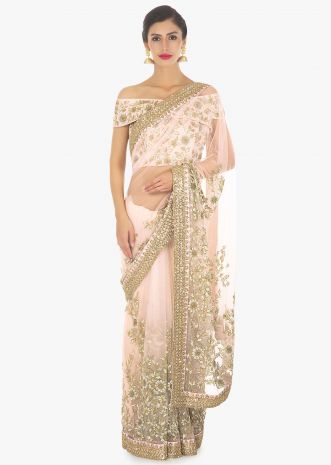 Powder pink heavily embellished net saree paired with matching raw silk off shoulder blouse