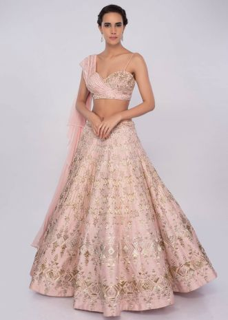 Powder pink raw silk lehenga teamed with one side strap bustier with georgette drape  only on kalki