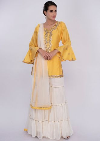 Yellow suit with white sharara and net dupatta only on Kalki