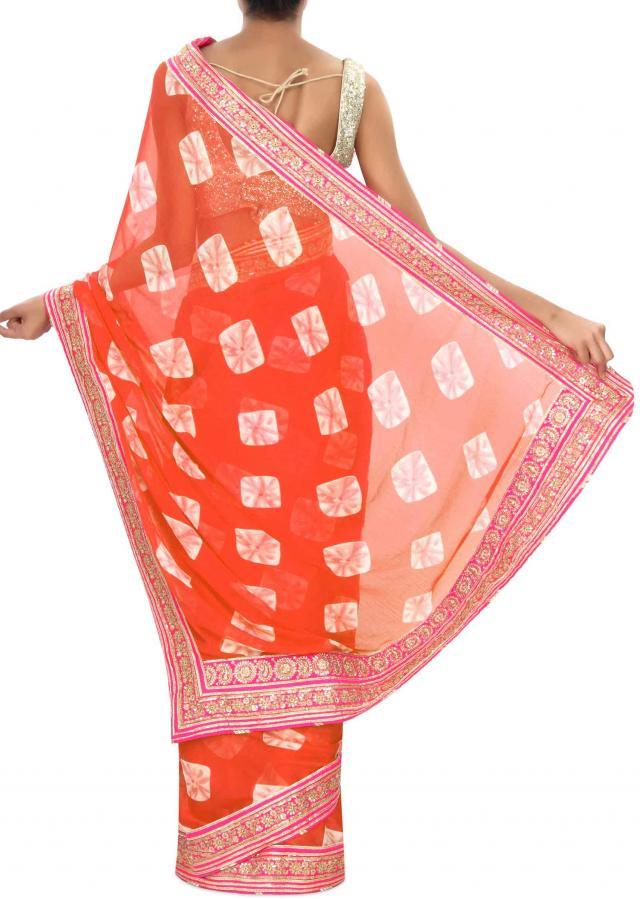 Orange bandhani saree embellished in zari embroidered border only on Kalki