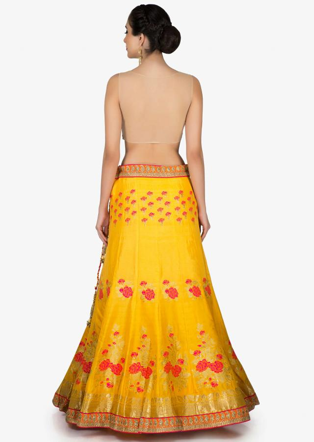 Amber yellow lehenga in floral motif with contrast rani pink dupatta in brocade only on Kalki