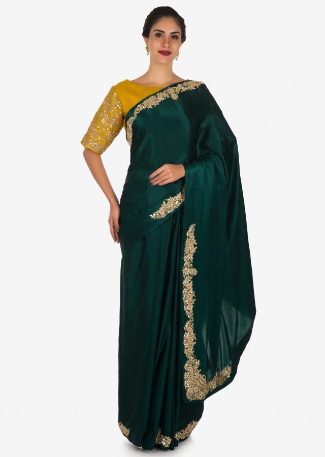 Bottle green saree in satin with mustard blouse beautified in zardosi and gotta patch work only on Kalki