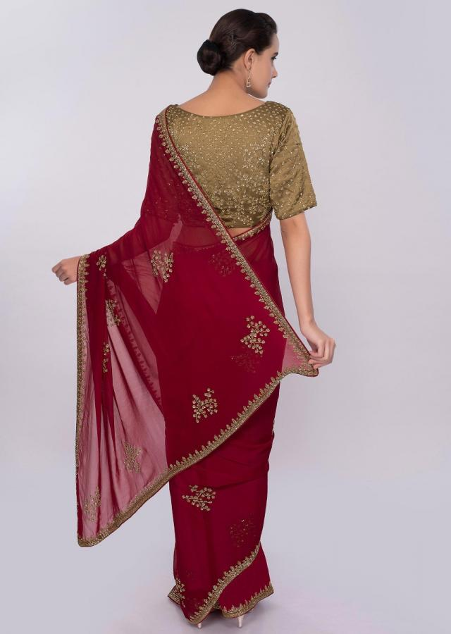 Brick red embroidered georgette saree with contrasting golden palm blouse only on Kalki