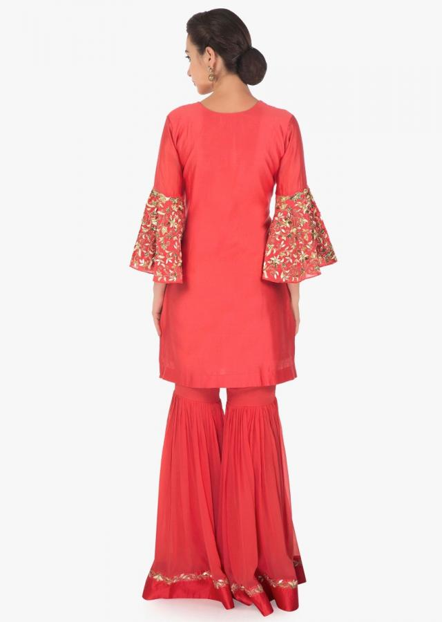 Coral peach A line suit with sharara pants is embellished in thread and gotta patch only on Kalki