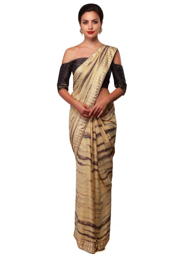 Cream and dark grey saree in batik print only on Kalki