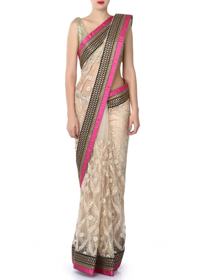 Polished cream saree enhanced in resham and zari lace only on Kalki