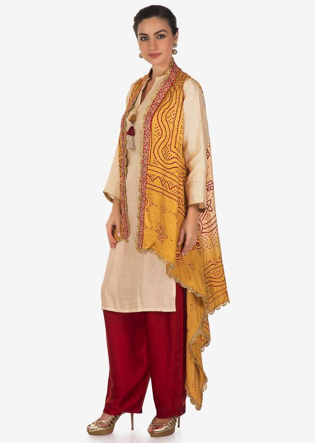 Cream suit with tassel matched with mustard bandhani jacket only on Kalki