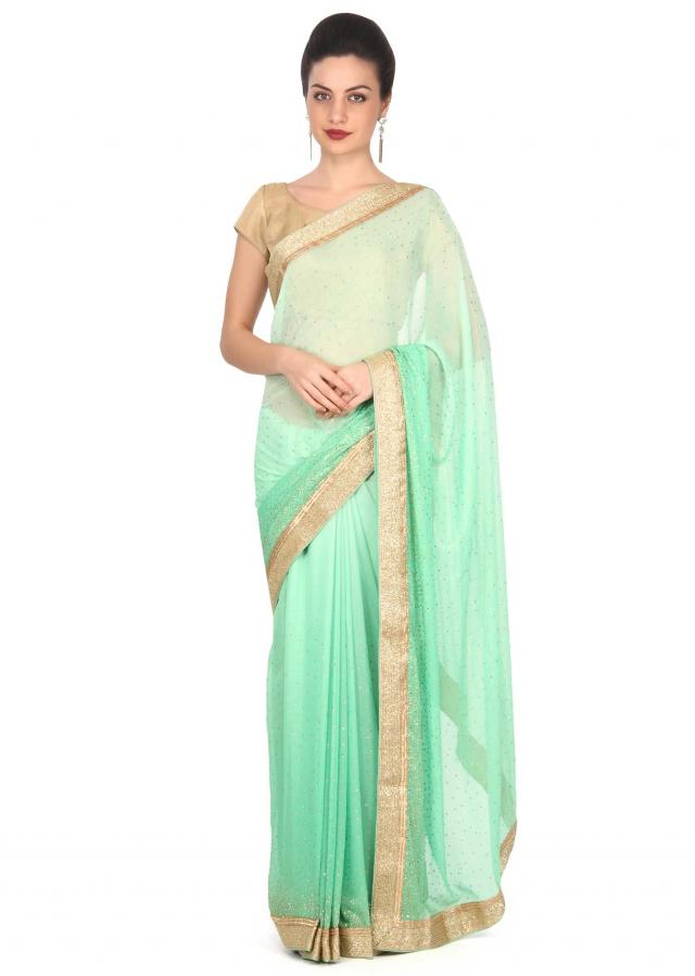 Green shaded saree adorn in kundan and kardana embroidery only on Kalki