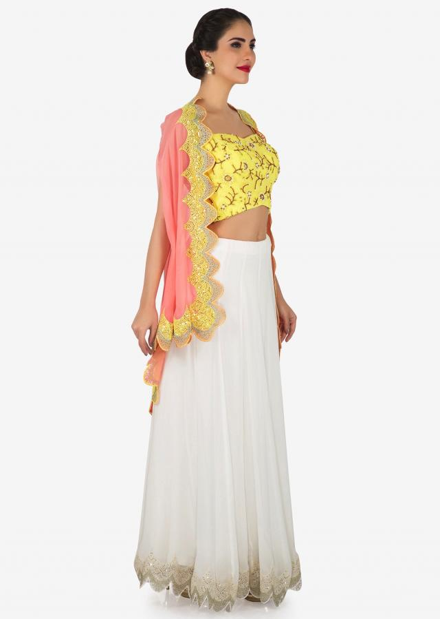Hand embroidered bright yellow and light peach jacket lehenga set only on Kalki