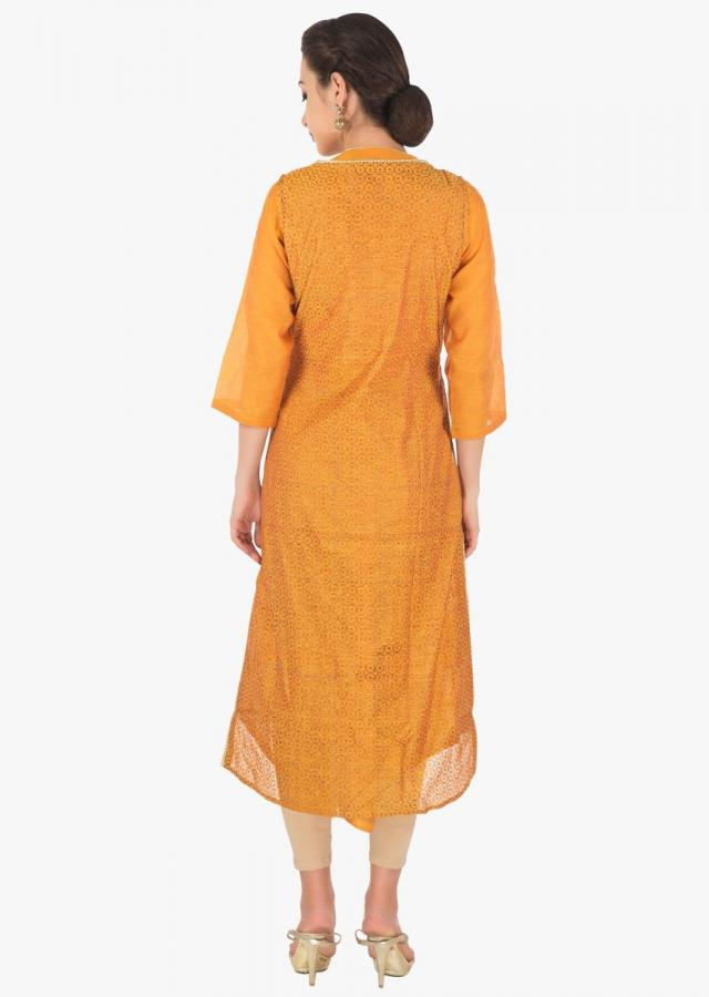 Mustard kurti in Tussar silk with fancy hem line in resham and zari butti only on Kalki