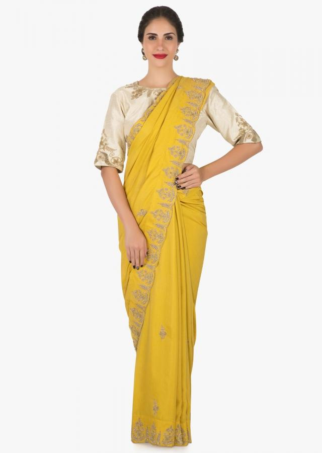Mustard saree with ready blouse in cream embroidered with zardosi and sequin work only on Kalki