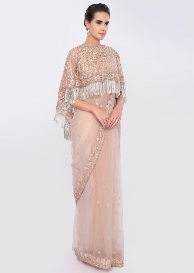 Pale peach embroidered net saree complemented with tasseled net cape only on Kalki