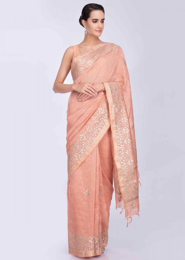 Pinkish peach linen saree with floral embroidered butti and border only on Kalki