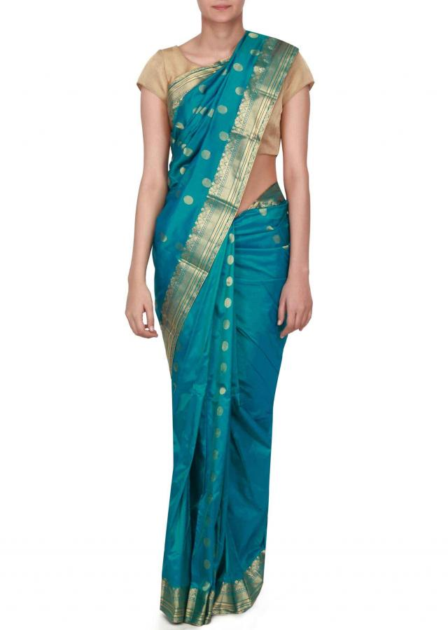 Teal green silk saree enhanced in weave embroidery only on Kalki