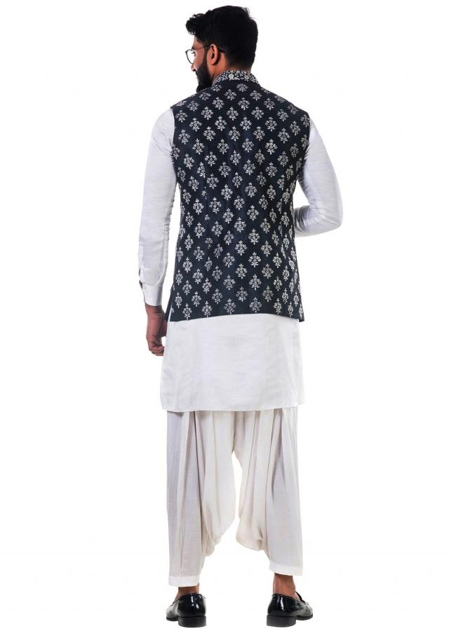 White linen satin kurta set with a  black silk nehru jacket with white cord floral embroidery only on Kalki